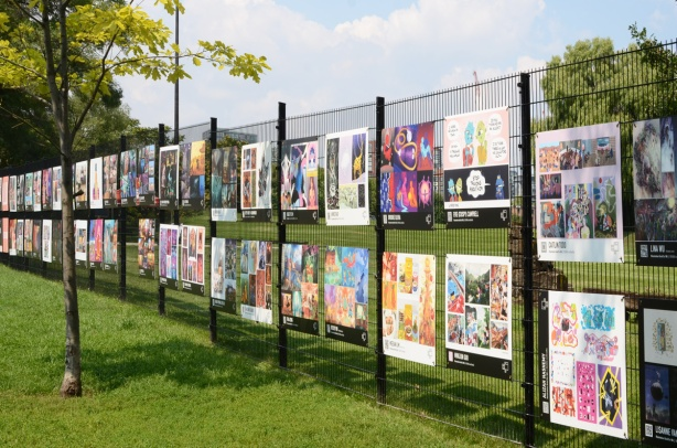 a section of fence around Fort York with artwork on it, exhibit of OCADU gradex for graduating illustration students