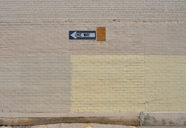 one way sign pointing left on beige brick wall