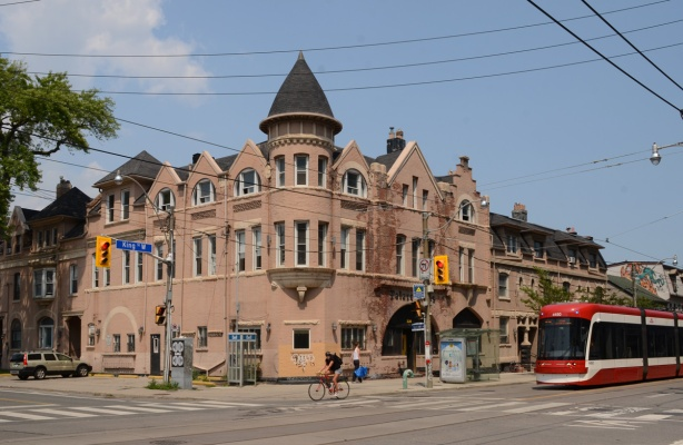 pinkish Palace Arms Hotel boarding house at King and Bathurst, with new TTC streetcar beside it