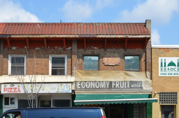 top of two storefronts, Economy fruit, and a pizza place