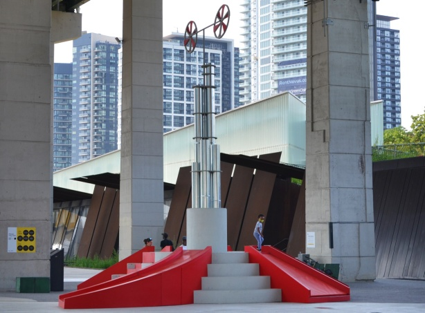 part of Playing in Public, an art installtion at the Bentway, small red slides with steps, in front of the old rusted metal walls near the entrance to Fort York