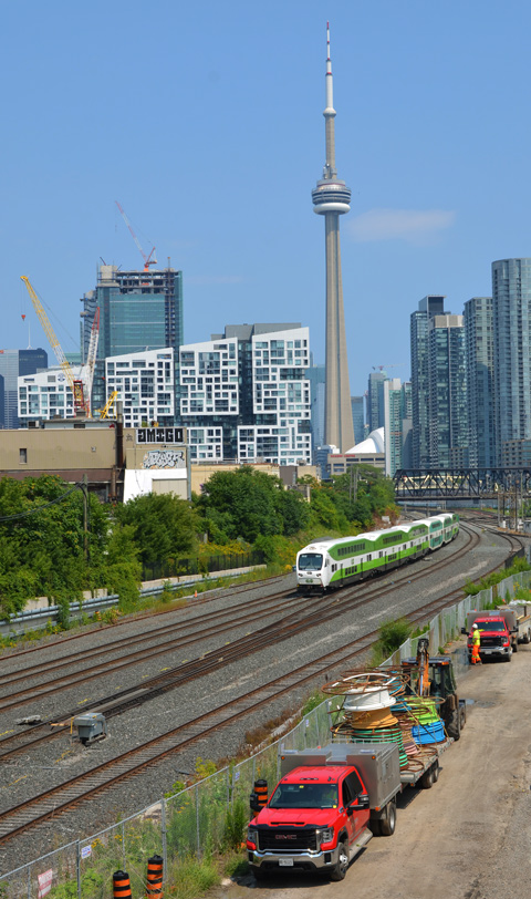 GO train on tracks, repair and maintenance trucks parked beside the tracks, CN Tower and downtown Toronto in the background