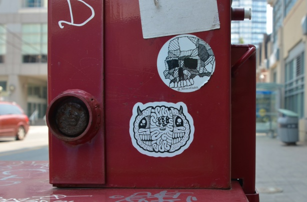 2 black and white stickers on a red newspaper box