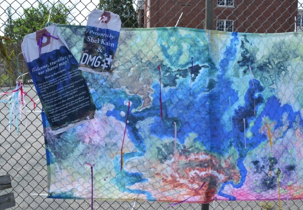an interactive art installation involving maps, on a fence outside Bloordale Collegiate