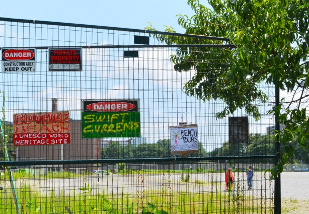 people walking across a vacant lot with signs on the fence around it. Danger swift currents, Beach tour advertisement,