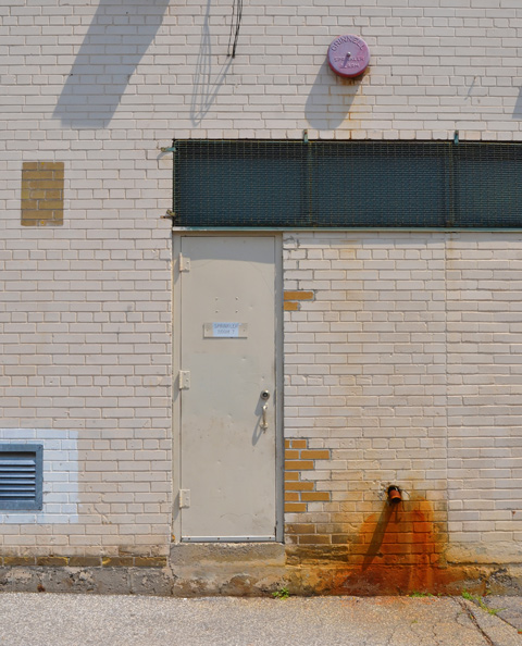 beige brick wall with beige metal door. sign on door says sprinkler room 7. rust marks on wall by overflow pipe