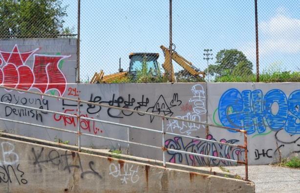 graffiti on concrete walls, with yellow digger parked behind fence