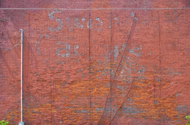 red brick wall with ghose sign for sweet caporals