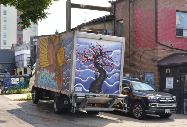 truck with street art painted on it, a tree with pink blossoms on the back and a bird with large wings on the side
