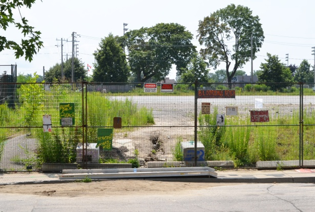 many signs on a fence surrounding a vacant lot