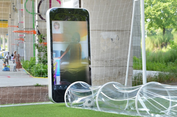part of Playing in Public, an art installtion at the Bentway, two screens looking like smartphones play videos of kids kicking soccer ball. a real ball passes through a see through plastic tunnel between the screens