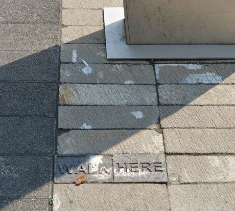 looking down at the sidewalk, the words walk here are pressed into a grey stone brick.