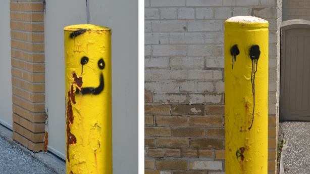 two yellow half posts in a parking lot, one with happy face and one with crying eyes