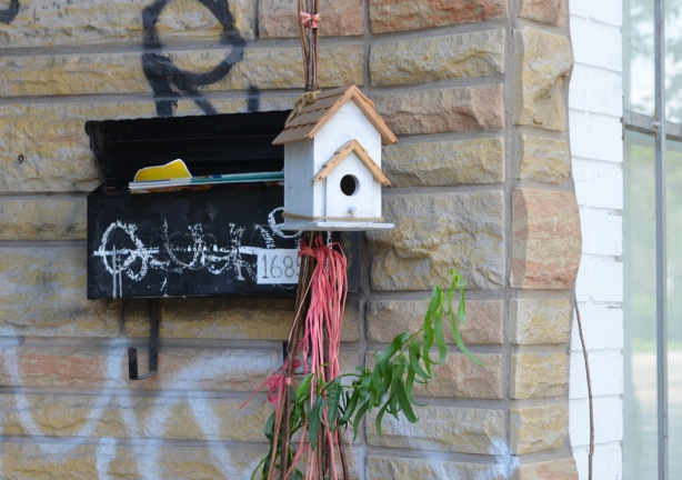 a small white bird house is attached to the end of a black mailbox in a doorway