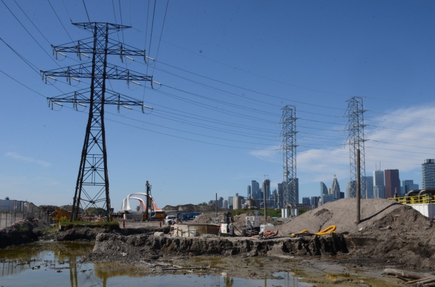 in the distance, new bridge for Commissioners Road, end of Commissioners Road, chainlink fence, road taken up, Toronto skyline behind