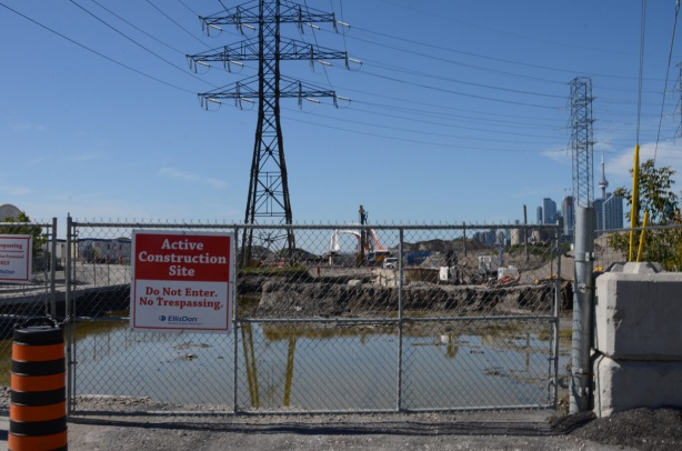 end of Commissioners Road, chainlink fence, road taken up, Toronto skyline behind