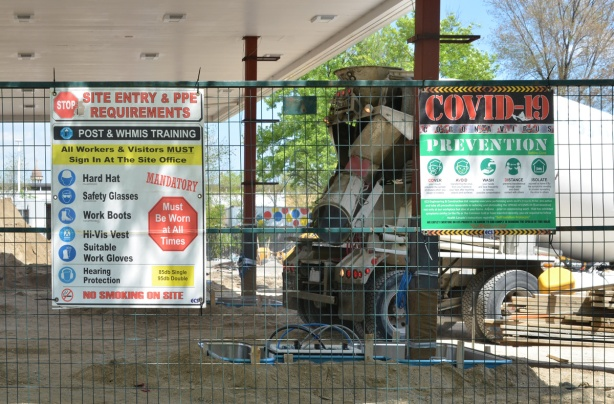 Coid prevention signs secured to a metal fence surrounding a construction site, a cement truck is working there