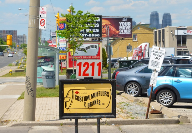 many signs for stores and businesses, posted beside the sidewalk,