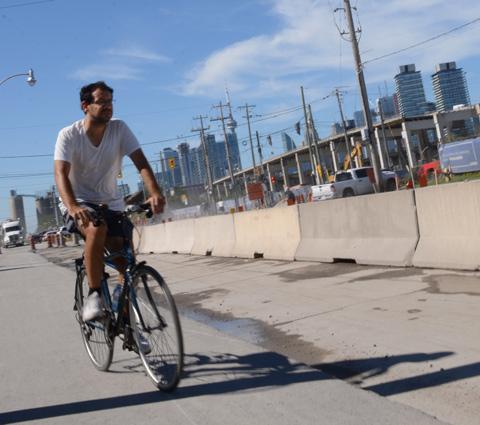 cyclist rides on the sidewalk past construction site in Port Lands, Gardiner demolition