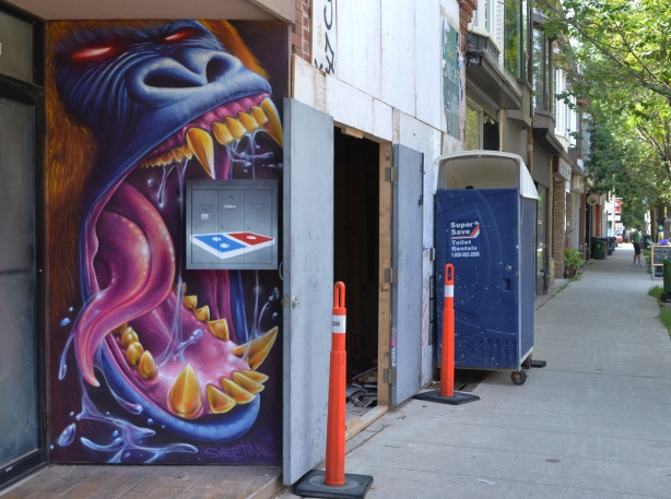 street art painting of a blue dragon with mouth open wide, pink tongue and yellow teeth, dominos pizza box in mouth