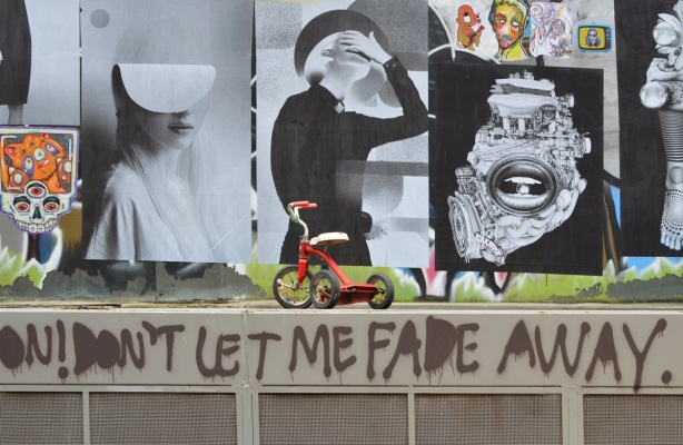 red trike at paste platz, wheatpaste papers on a wall, with words Don't let me fade away