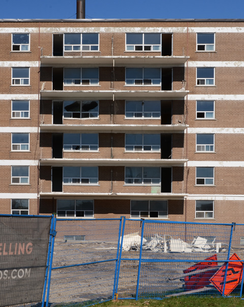 brick apartment building with balconies, empty, some broken windows, some white debris in a pile in front, blue construction fence