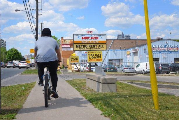 a man rides his bike on the sidewalk on Kennedy Road with back to camera