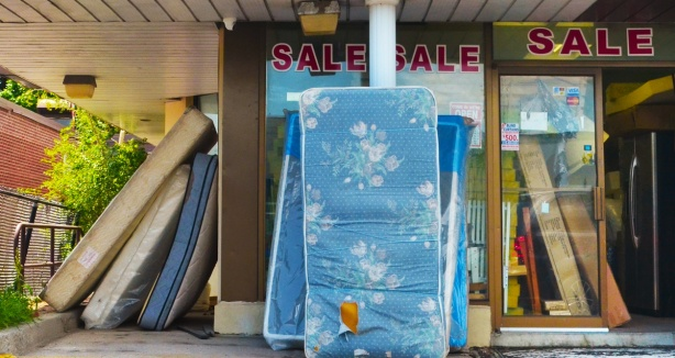 mattresses on display outside a store, leaning against the pillars of the building