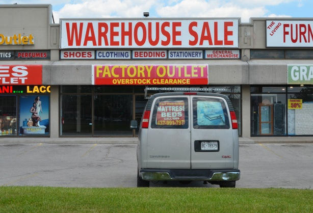 a van parked out front of a store with signs, factory outlet, warehouse sale, sign in back window of van advertising a mattress sale