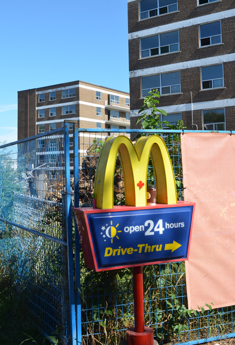 yellow arches mcdonalds sign pointing to drive thru, open 24 hours, in the background, 2 brick apartment buildings that are empty. blue construction fence between, buildings are about to be demolished