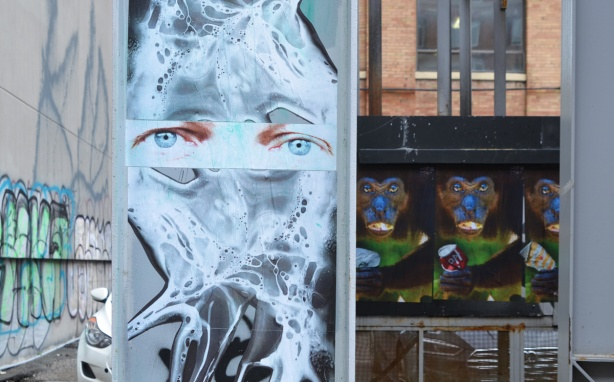 paste platz, wheatpaste papers on a wall, monkeys with cans, jumbleface with blue eyes and blob face