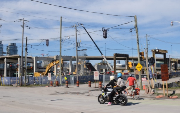 motorcyclists wait for traffic light at intersection of Don Roadway and Villers, construction behind them, removal of eastern portion of the Gardiner Expressway