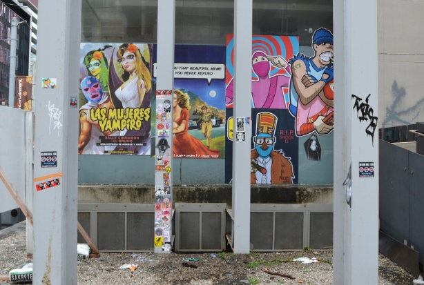 paste platz, wheatpaste papers on a wall, 2 steel poles in front covered with stickers, wall behind with large paper posters pasted on