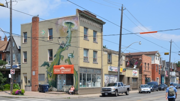 northeast corner of College and St. Clarens, three storey beige brick building with coin laundry on ground floor, large beanstalk mural up the side of the building