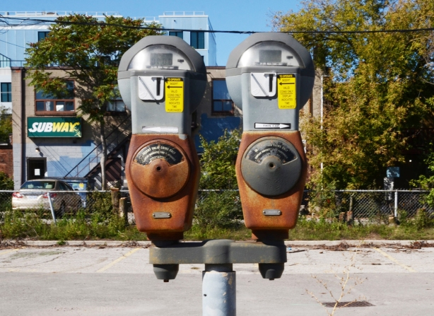 a pair of old coin fed parking meters still standing on their metal pole in an abandoned parking lot
