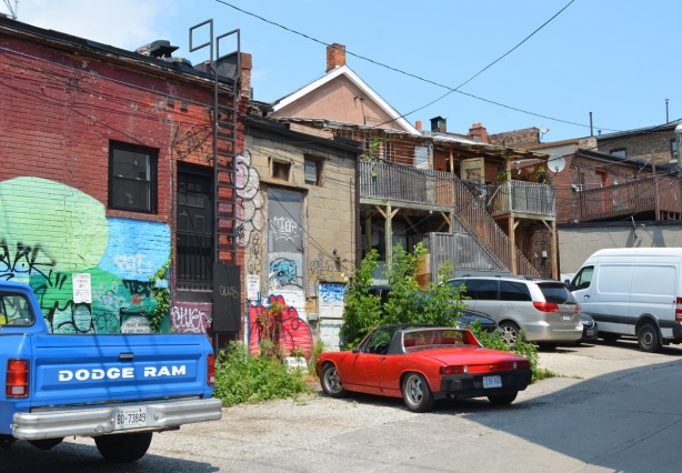 backs of stores in a small alley where a blue Dodge Ram pickup truck is parked. Also parked is an orange car, an old porsche convertible. Graffiti on some of the buildings