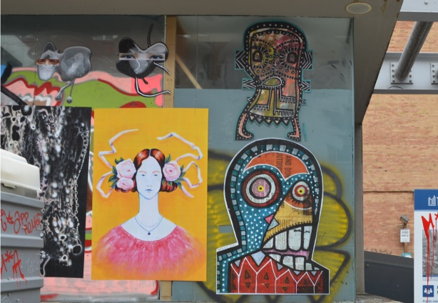 paste platz, wheatpaste papers on a wall, woman with large buns of hair at ears, with pink roses there too, also colourful abstract faces