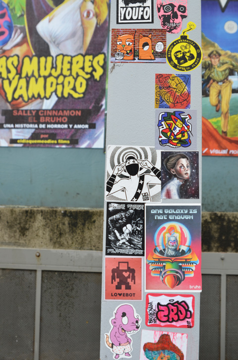 paste platz, wheatpaste papers on a wall, stickers on a beam in front of larger posters