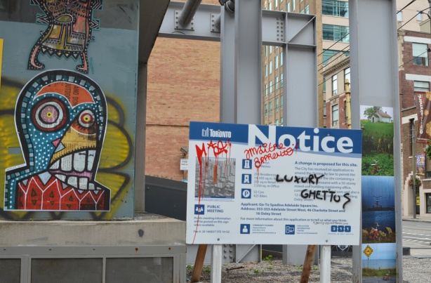 paste platz, wheatpaste papers on a wall, with blue and white city of Toronto development notice sign, black graffiti says luxury ghettoes