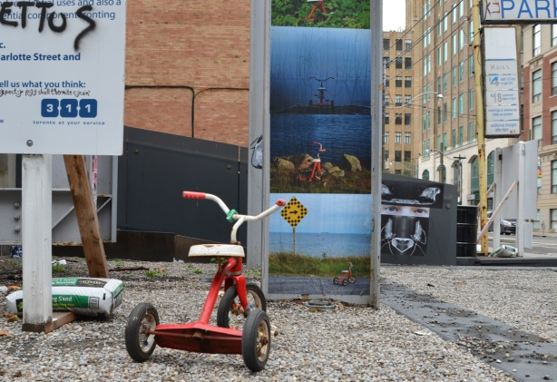 llittle red trike in front of a series of photos that feature the trike, paste platz in downtown Toronto, a large paste up display