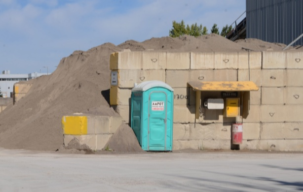 port a pottie by a wall holding back a pile of sand