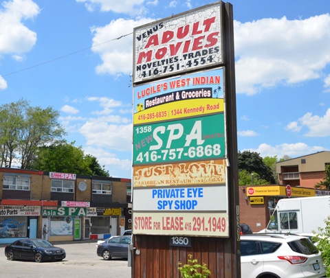 large sign in front of plaza listing all the stores, adult movies, spa, private eye spy shop,