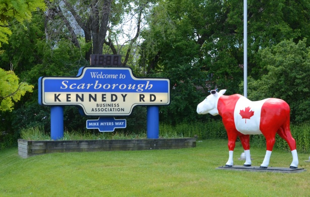 a stature of a life sized moose painted like a Canadian flag beside a large welcome to Scarborough sign, from Kennedy BIA.