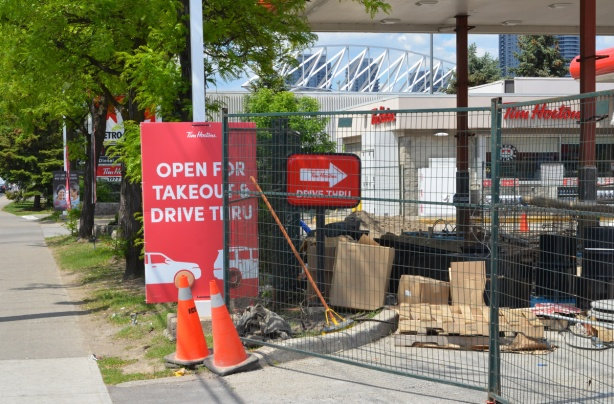 construction fence around a Tim Hortons and Petro Canada station, sign says open for takeout and drive thru