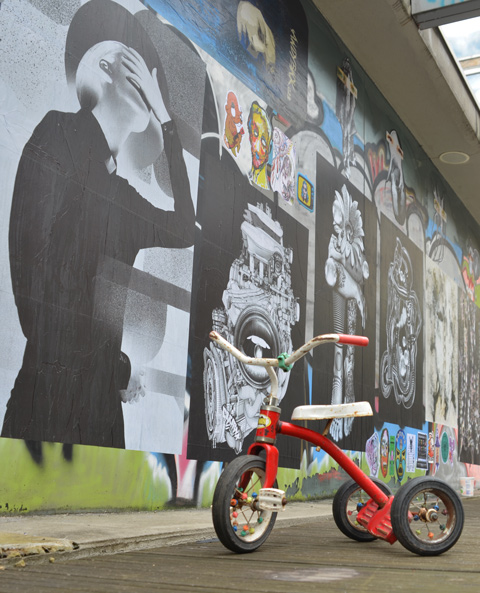 red trike in front paste platz, wheatpaste papers on a wall