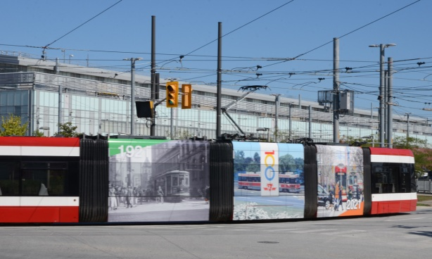 TTC streetcar leaving Leslie Barns, sides are decorated with pictures commemorating 100 years of the TTC