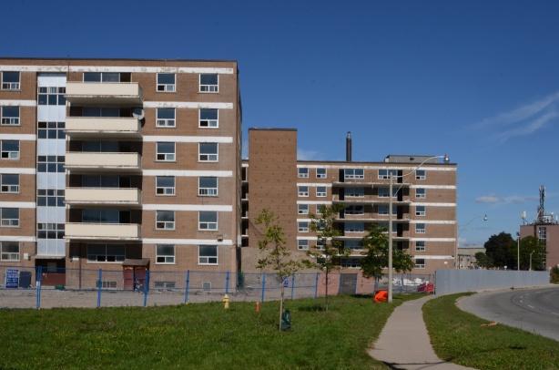 sidewalk along Eastern Avenue, green grassy boulevard, empty apartment buildings behind chainlink fence