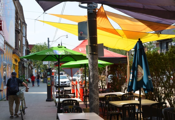 man walking on sidewalk, away from the camera. patio on street beside sidewalk with many umbrellas over the tables, green, red, and yellow