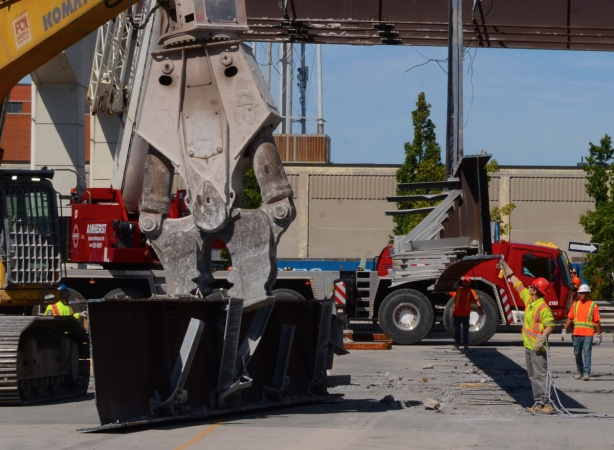 men helping a crane to direct a girder down to the ground while another machine breaks another girder to get it ready to go in truck