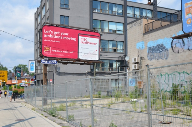 billboard in vacant lot with chainlink fence around it